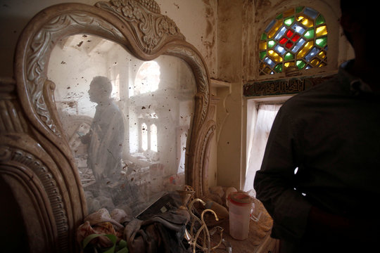 A man looks from a mirror in a house which was destroyed by a Saudi-led air strike in old Sanaa city