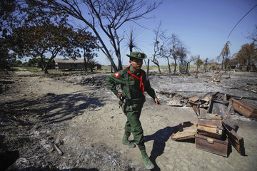 A soldier walks amid the rubble of a neighbourhood in Pauktaw township that was burned in recent violence