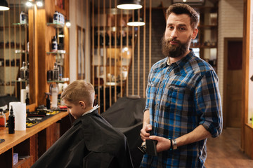 Nice good looking barber holding a comb