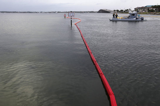 Escambia County Oil Spill Response workers set oil containment booms near the bridge to Pensacola Beach