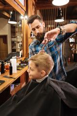 Nice cute boy visiting a barbershop