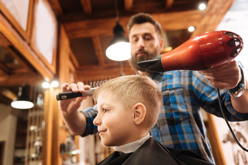 Cute positive boy visiting a hairdresser