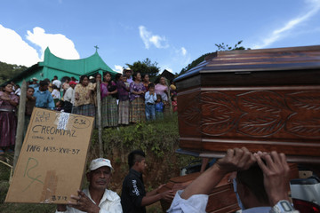 People carry a box containing the skeleton of one of six people who disappeared during the internal armed conflict, and a coffin to place the bones, outside the entrance of a church in the village of Pambach