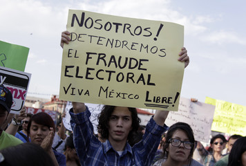 """An university student holds a placard during a """"yo soy 132"""" protest in demand of balance in the media coverage of the presidential race in Monterrey"""