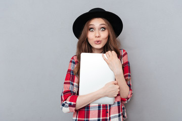 Smiling woman in plaid shirt holding laptop