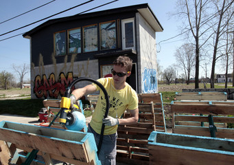 Darin McLeskey, 22-years-old, spray paints wooden pallets he plans to use to build a fence around a garden next to one of the properties he purchased and plans on refurbishing in Detroit