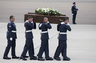 The coffin of Ann McQuire is carried from an RAF C-17, which repatriated the bodies of nine British nationals killed by a gunman in an attack at the Tunisian beach resort of Sousse, in RAF Brize Norton