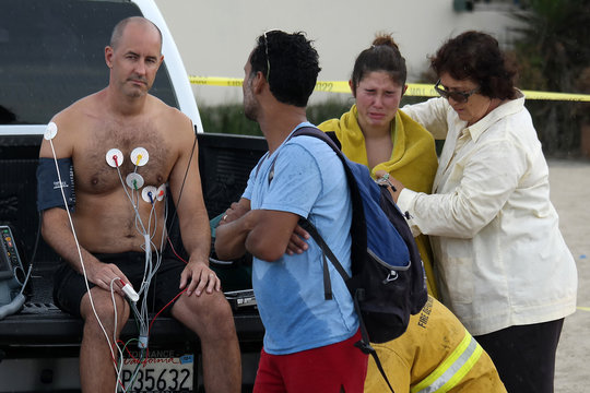 Man is treated by paramedics while a woman is comforted after a lightning strike in Venice