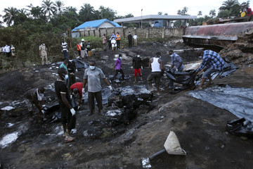 Rescue workers collect charred bodies of victims of fire explosion after fuel tanker overturned along east-west road in Nigeria's oil hub city of Port Harcourt