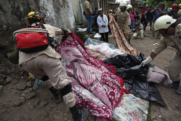 Firefighters cover the bodies of victims of a landslide  in Tegucigalpa