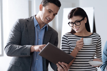 Positive delighted colleagues looking at tablet