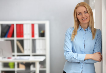Blonde business woman in the office with copy space. Smiling and looking camera.