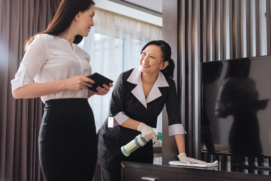 Joyful nice businesswoman talking to a hotel maid