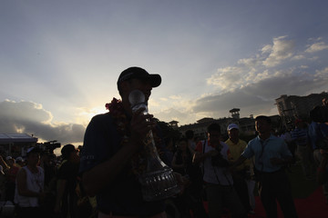 Kuchar of the U.S. poses for pictures with his team's trophy after he won Mission Hills World Celebrity Pro-Am golf tournament in Haikou