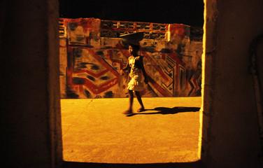 A girl walks with a bowl on her head in Vridi's Village Rasta, Abidjan