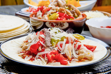 Beef and chicken  Fajitas with colorful bell peppers in  tortilla bread and sauces