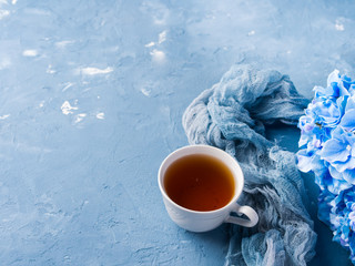 Cup of tea on blue background with flowers and textile
