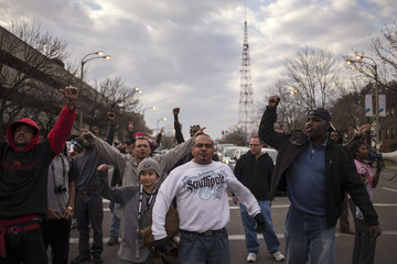 Protesters, demanding justice for Michael Brown, shout towards police in riot gear outside the Edward Jones Dome in St. Louis