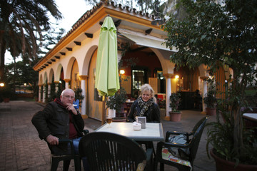 British landscape architect Judy Rawlings and her friend, historian Meirion Hughes, pose for a photo as they sit at a bar in Marbella