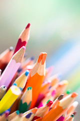 Stack of different color wooden pencil with orange color stand out on a bright green background as...
