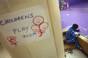 A young boy colors with crayons in the children's playroom at a Red Cross shelter in Hampton Bays, New York
