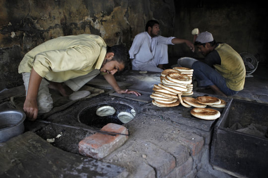 A baker looks for baked bread in his oven at his shop in New Delhi