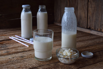 Sour-dairy drink or yoghurt in bottle that come from the kefir grains and milk on wooden background. Photographed with natural light