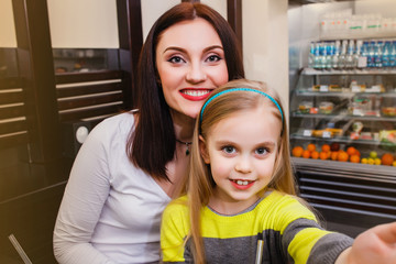 young mother with her little dauther at a table in a cafe makes selfie
