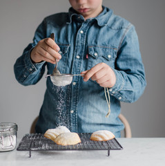 boy sieving icing sugar on freshly baked madeleines cookies cake