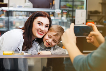 A man makes picture of young mother with her little son at a table in a cafe