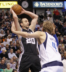 San Antonio Spurs guard Ginobili passes the ball as Dallas Mavericks forward Nowitzki defends during their NBA basketball game in Dallas, Texas