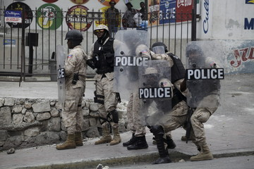 National Police officers protect themselves from rocks thrown by protesters during a demonstration against the electoral process in Port-au-Prince, Haiti