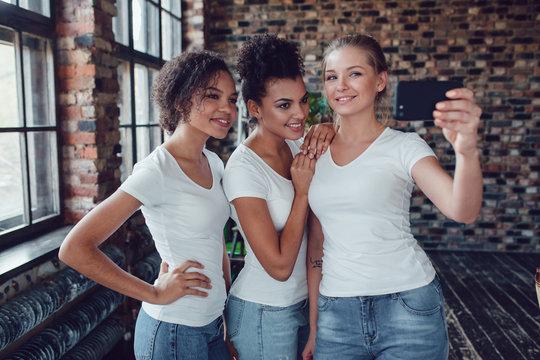 Three attractive girls in white T-shirts make selfie near the window.