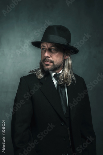 Retro victorian style man with blond long hair and hat. Wearing black suit  and tie. a7ac1389771