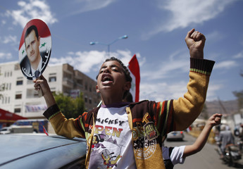 A boy holds a sign with a picture of Syrian President Assad as he shouts slogans during a demonstration to show his support, outside the Syrian embassy in Sanaa