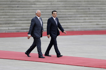 Malaysia's Prime Minister Najib Razak and China's Premier Li Keqiang attend a welcoming ceremony in Beijing