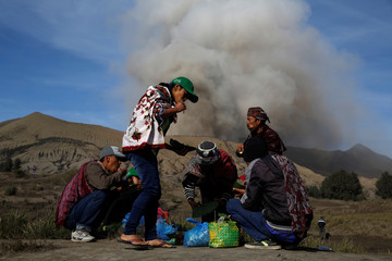 Mount Bromo spews ash as Hindu villagers take their breakfast ahead for Kasada ceremony, when villagers and worshippers throw offerings such as livestock and other crops into the volcanic crater of Mount Bromo, in Probolinggo
