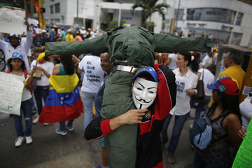Opposition student carries a doll wearing a military uniform during a rally against violence in Caracas