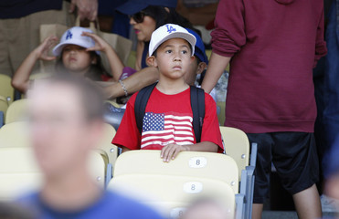 Eight-year-old Villasenor of Fontana wears a t-shirt with a U.S. flag while keeping an eye on batting practice prior to the MLB baseball game between the Cincinnati Reds and Los Angeles Dodgers in Los Angeles