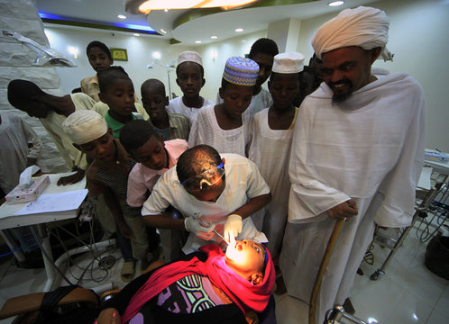 Dentist and CEO of Khartoum Dental Clinic Dr Fadil Elamin teaches oral hygiene to children and a sheikh from Khalwas of the Jabel Awlia district in Khartoum