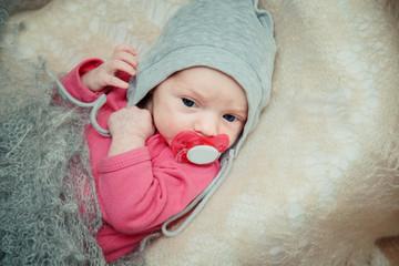 Newborn baby lies in a crib.