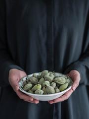 Grüne Mandeln in einer Schale von Frau in Händen gehalten