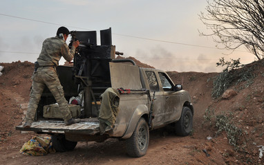 A Kurdish People's Protection Units (YPG) fighter fires his weapon towards forces from the al Qaeda-linked Islamic State in Iraq and the Levant (ISIL) in Al Rawiya