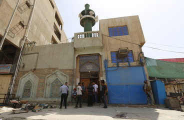 People gather at site of suicide bomber on Shi'ite mosque in Baghdad.