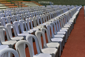 Rows of white folding chairs on lawn before a graduation ceremony in summer time