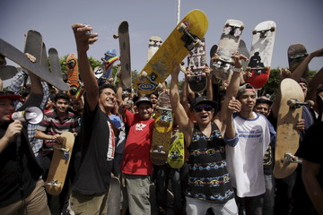 Skateboarders pose for pictures on Go Skateboarding Day in San Salvador