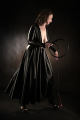 woman in black dress with whip in her hands