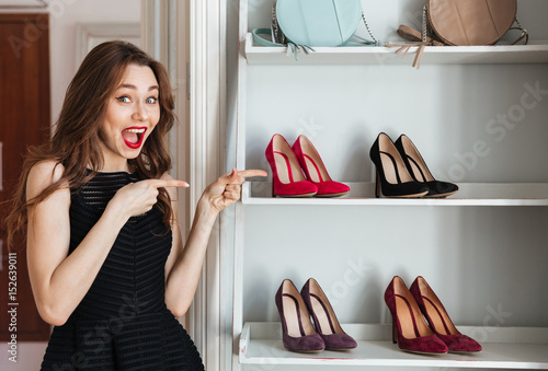 """Happy young woman choosing shoes and pointing."" photo ..."