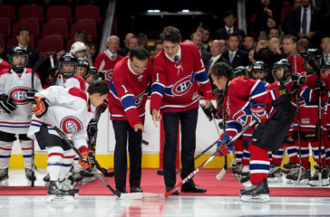 Canada's Prime Minister Justin Trudeau and Chinese Premier Li Keqiang drop the puck in a ceremonial face off with young hockey players at the Bell Centre in Montreal