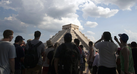 Tourists watch Kukulcan Castle, one of the seven wonders of the modern world, at the archaeological site of Chichen Itza during the spring equinox, at the Yucatan Peninsula